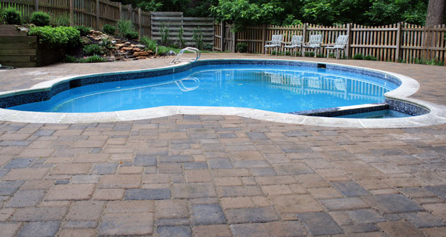 Paver patio swimming pool surrounds are cool, comfortable, non-slip, good looking, and low maintenance.