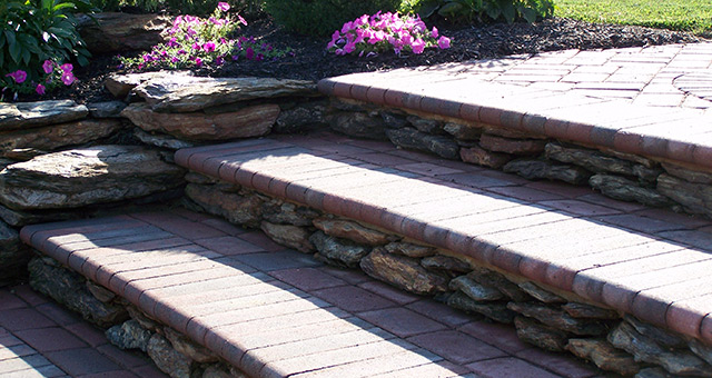 Natural stone and paver steps connecting to paver pathway.